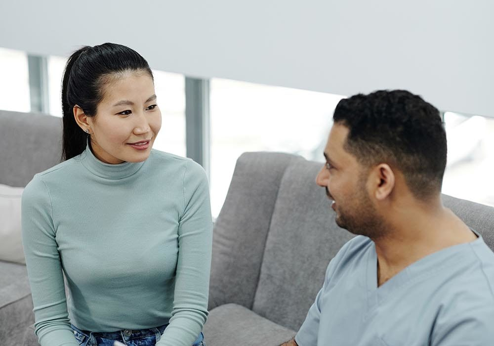 woman sitting on couch speaking to doctor